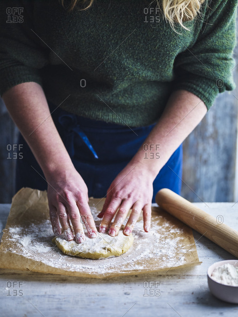 Pastry being made by hand and rolled out with a rolling pin