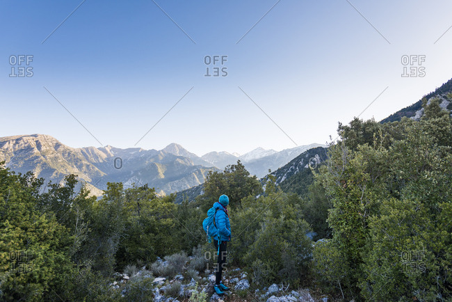 A woman trekking in Greece looks out at Mount Taygetus the highest peak on the Peloponnese