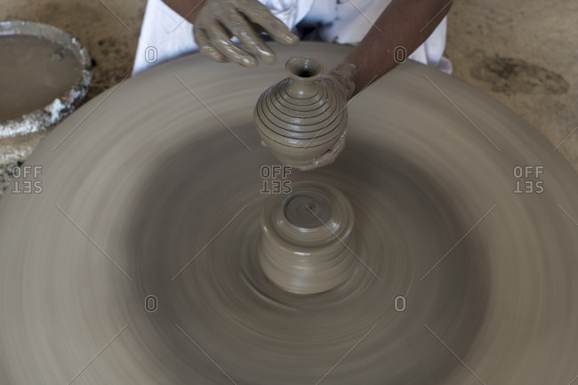A potter in a Bishnoi village near Jodhpur making a clay pot on a spinning wheel