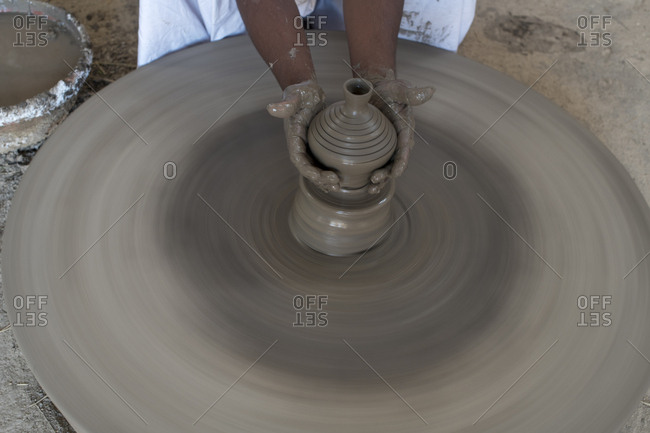 Potter in a Bishnoi village near Jodhpur works on a clay pot on a spinning wheel