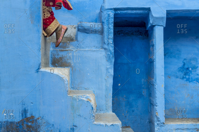 An Indian woman wearing a red Sari climbs some steps painted the typical blue color in Jodhpur in India