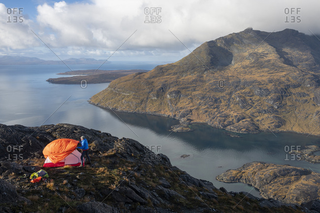 Man camping on the top of Sgurr Na Stri on the Isle of Skye in the Scottish Highlands with views towards Loch Coruisk and the main Cuillin ridge