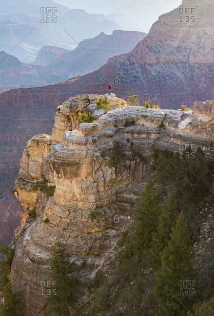A man stands on a thin rocky promontory overlooking the Grand Canyon near Mather Point
