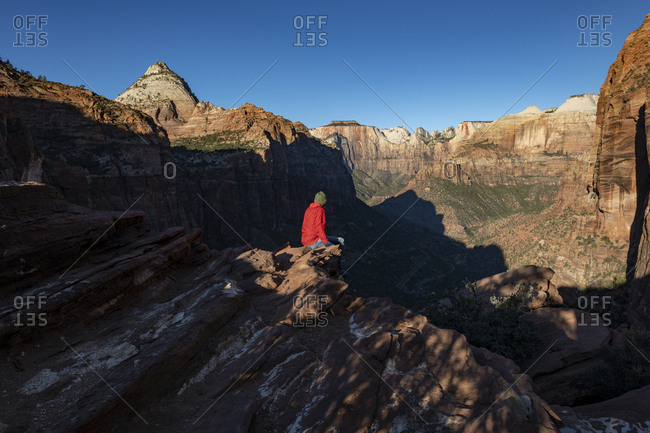 A man looks out at a canyon from a viewpoint on rocky ledge at Zion National Park in Utah