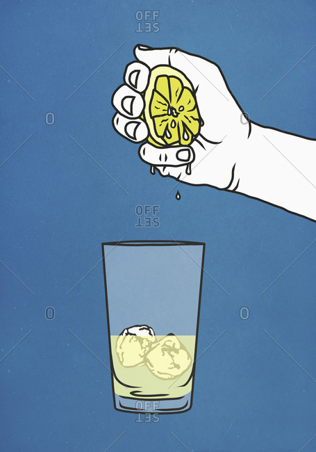 Hand squeezing fresh lime into glass with ice
