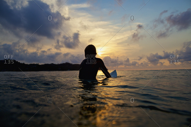Silhouette surfer sitting on surfboard in tranquil ocean at sunset, Sayulita, Nayarit, Mexico