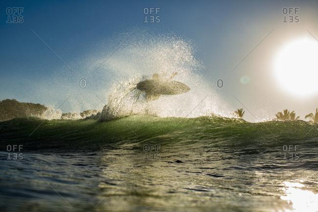 Surfer catching air behind ocean wave at sunrise, Sayulita, Nayarit, Mexico
