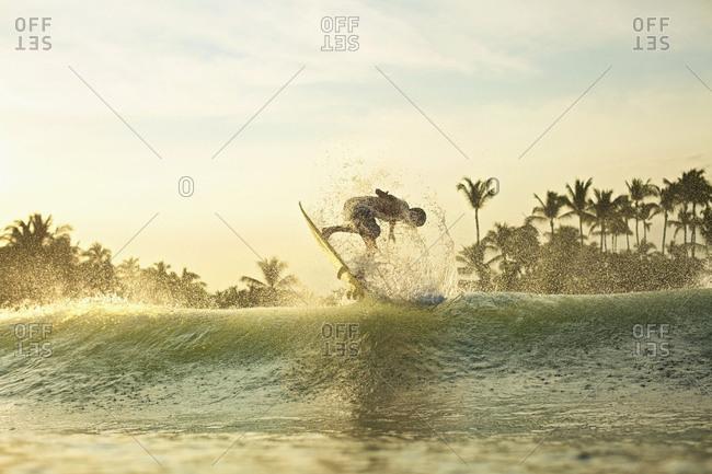 Male surfer catching air behind ocean wave at sunrise, Sayulita, Nayarit, Mexico