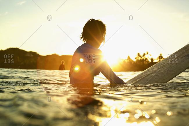 Female surfer on surfboard on sunny ocean at sunrise, Sayulita, Nayarit, Mexico