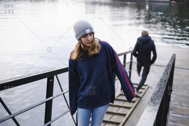 Teenage girl walking up ramp over Shawnigan Lake, British Columbia, Canada