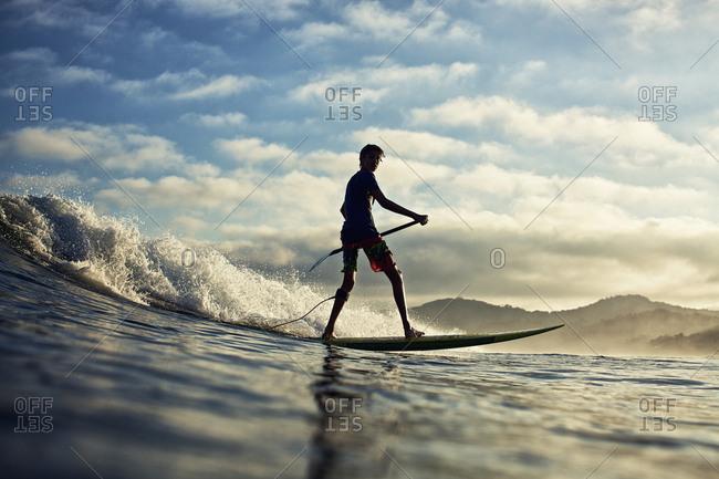 Silhouette boy paddleboarding over ocean wave, Sayulita, Nayarit, Mexico