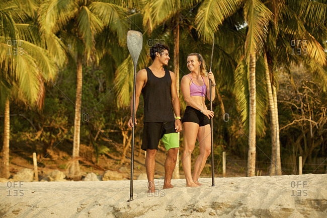 Young couple with oars on sunny, tropical beach