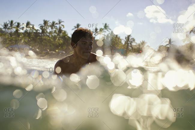 Young man swimming in sunny, tropical ocean, Sayulita, Nayarit, Mexico