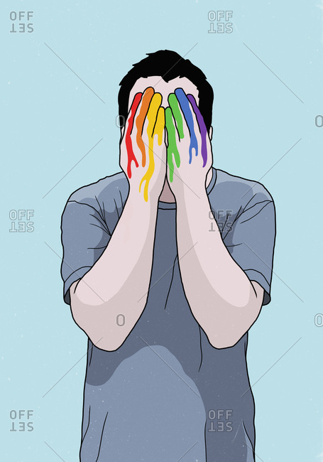 Man covering face with rainbow painted hands