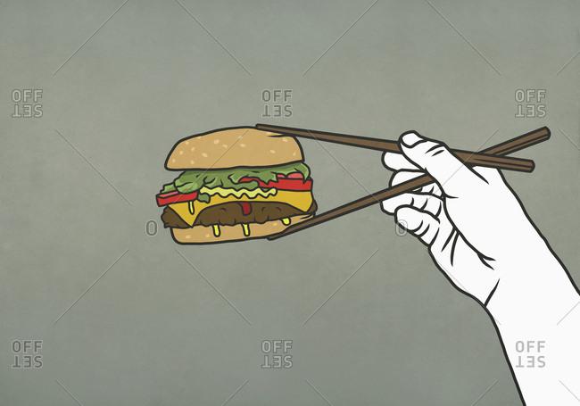 Man eating cheeseburger with chopsticks