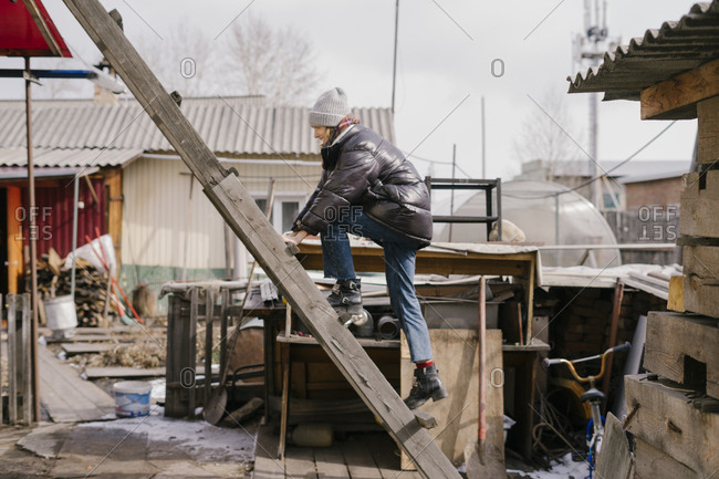 Young beautiful woman climbs a wooden staircase to the roof of a village house