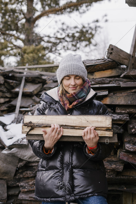 A young beautiful woman at her grandmother's in the village holding firewood for the stove or grill