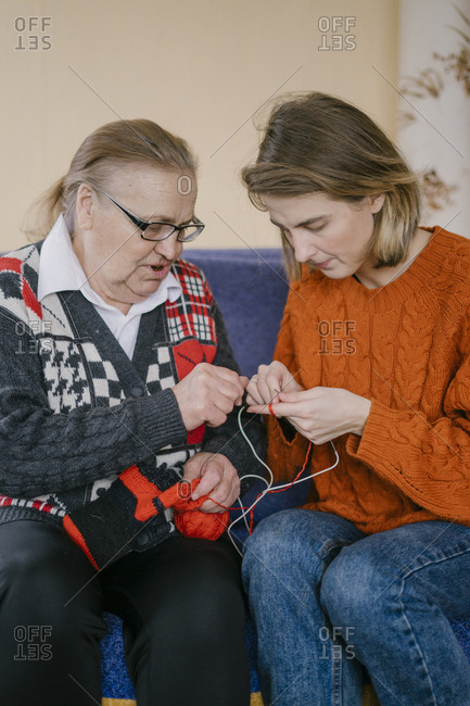 Grandmother teaches granddaughter to knit hat and socks with crochet and yarn