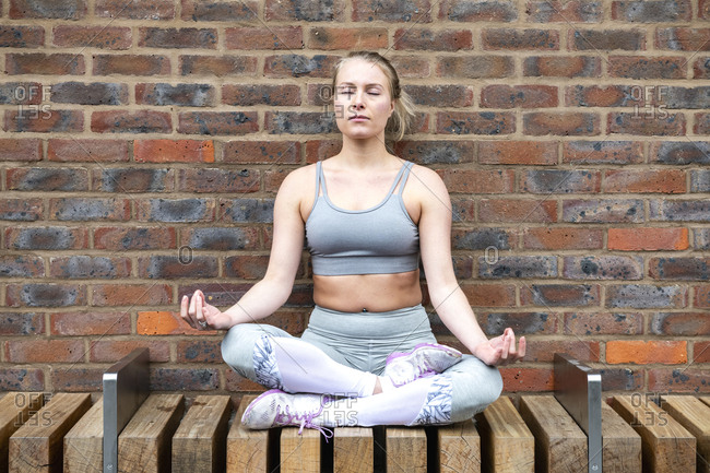 Woman sits in lotus position with her eyes closed