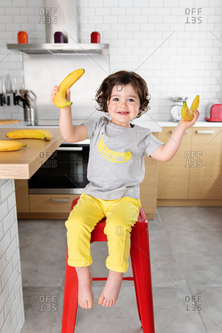Smiling young child pretending to lift weights with bananas