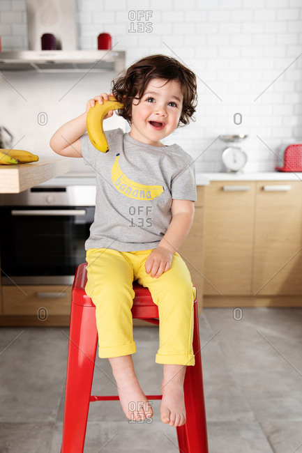 Smiling child pretending to phone with a banana