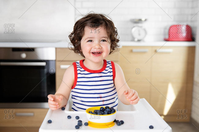 Happy toddler in high chair eating blueberries