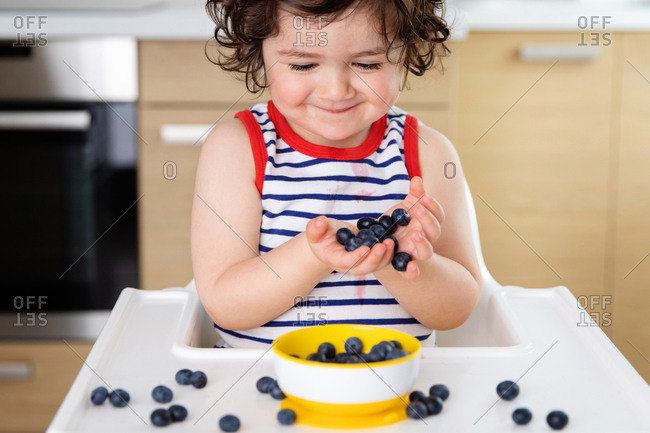 Smiling toddler in high chair holding blueberries in hands