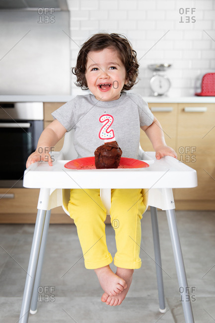Smiling child in high chair with cake celebrating second birthday