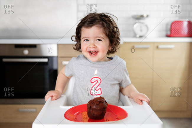 Happy toddler in high chair with cake celebrating second birthday