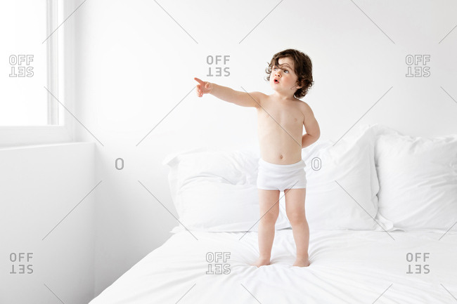 Toddler standing on bed pointing with finger