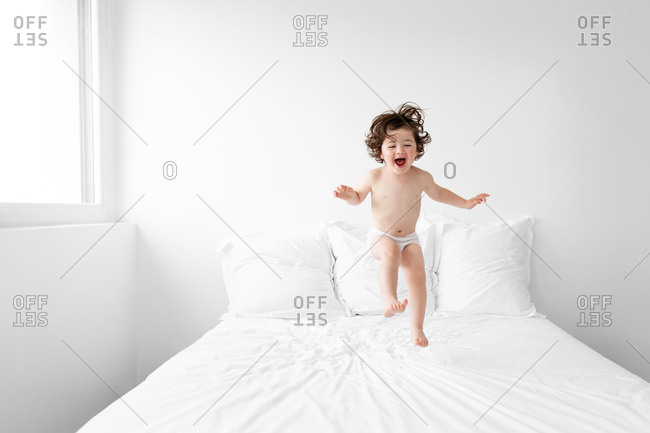 Happy toddler in underwear jumping on bed