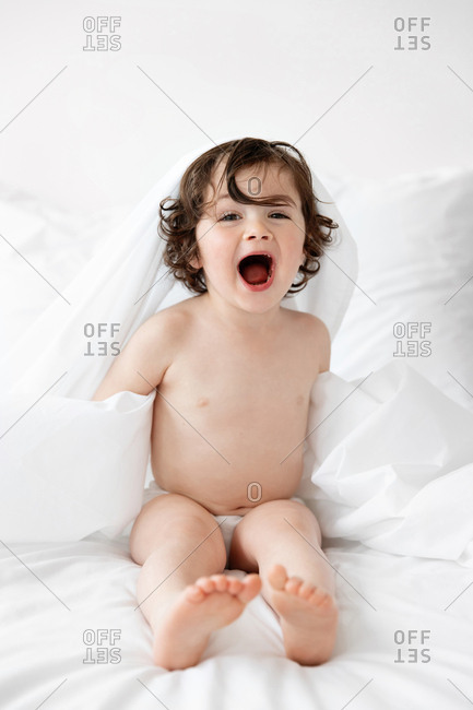 Happy toddler playing on bed with white sheet