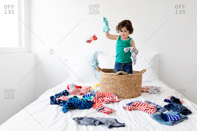 Young child standing in laundry basket throwing clothes