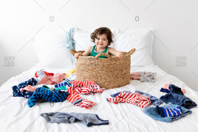 Funny toddler sitting in laundry basket