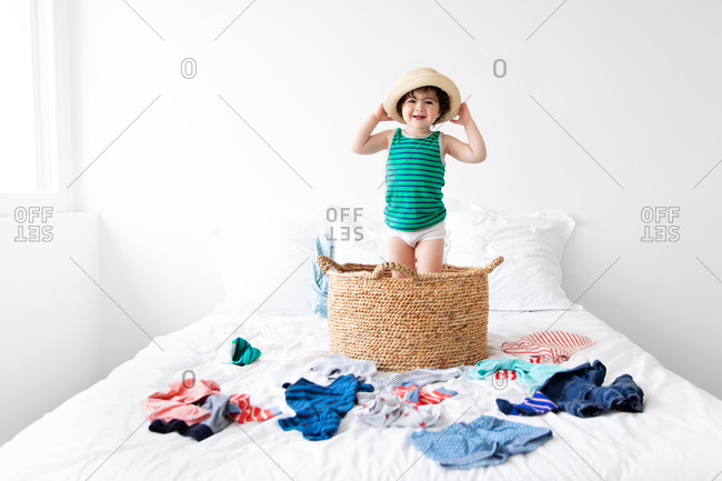 Happy child standing in laundry basket wearing sun hat