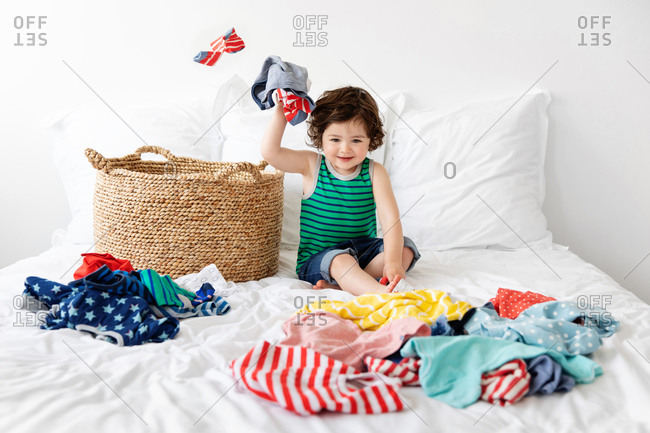 Happy toddler sitting next to laundry basket making mess with clothes