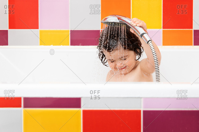 Toddler in bathtub rinsing hair with shower head