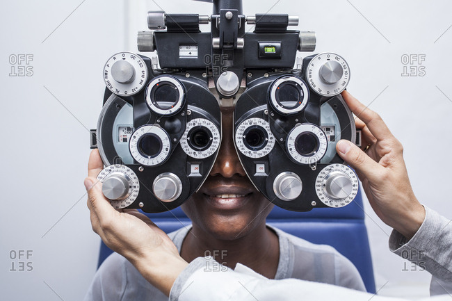 Studying a woman's eyesight with a phoropter