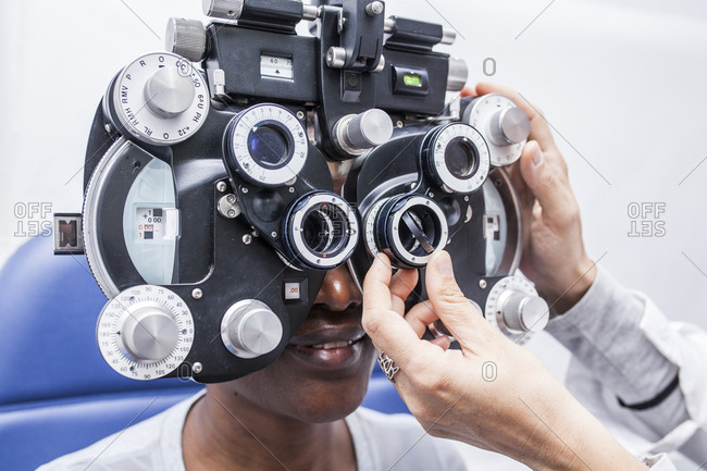 Studying a woman's eyesight with a phoropter, side view