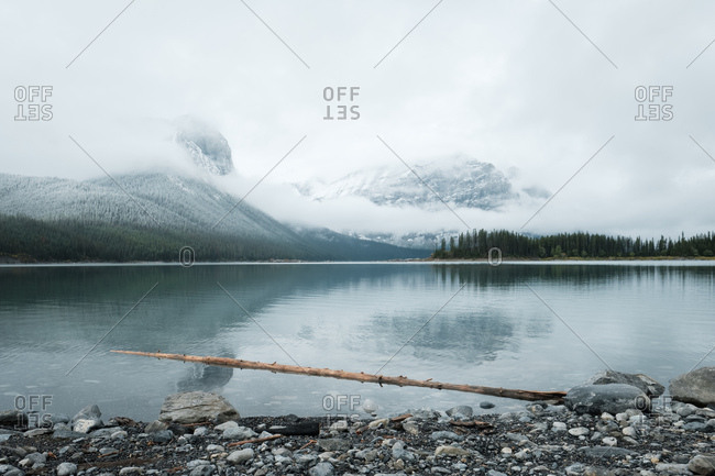 Snow-tinged mountains shrouded by clouds beyond a clear lake