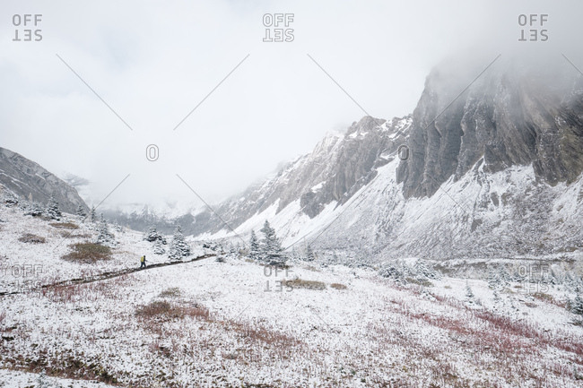 Hiking through the first snowfall in a mountain valley