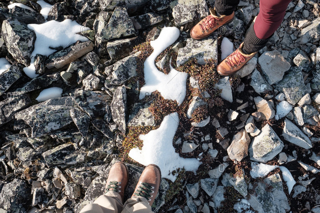 Hikers' feet stand atop rocks covered with snow and rock lichen