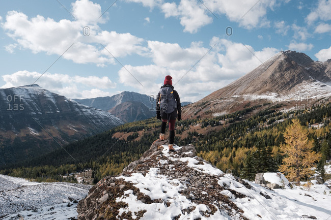 Female hiker overlooks trees and snow in mountain valley
