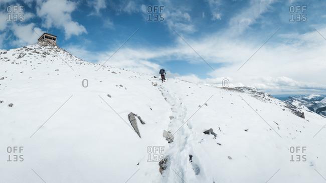 Female hiker treks upwards through snow to abandoned building at mountain peak