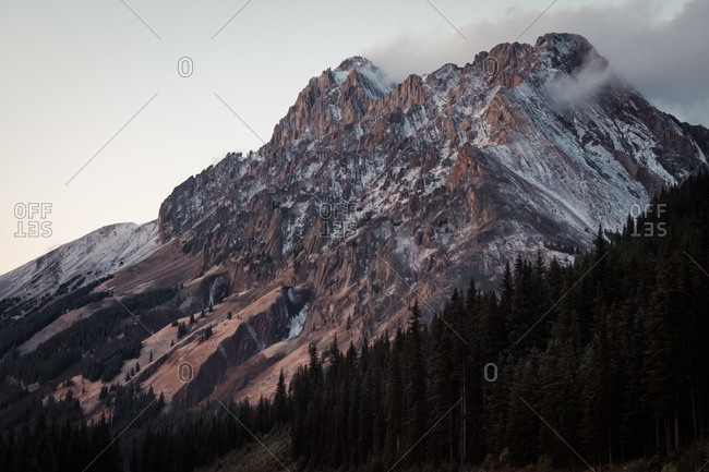 Soft evening light washes over rugged snow-kissed mountain peak