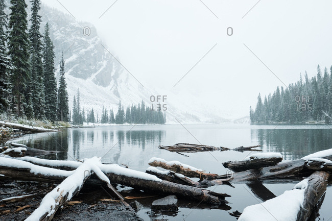 Fresh snow delicately coats the trees and mountains around a tranquil lake
