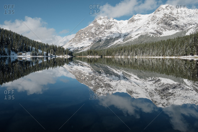 Perfect reflection of snow-tinged mountains, forest and blue sky in glass-like lake