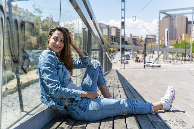Young woman sitting on the ground in Barcelona