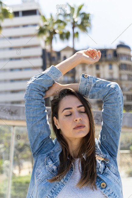 Young woman with arms raised and closed eyes