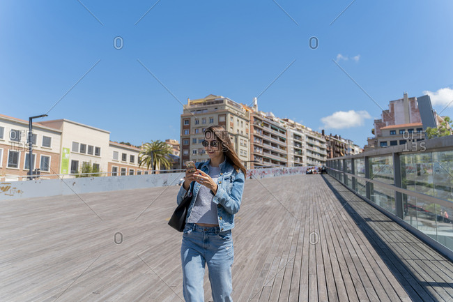 Young woman using smartphone on pedestrian bridge in Barcelona